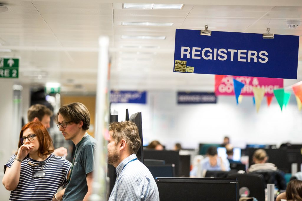 The Register team taking part in a standup and the Register sign