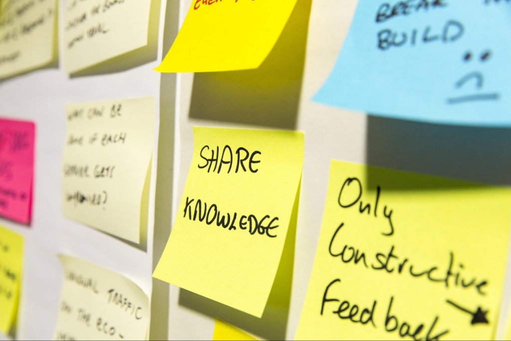 post-it notes on a wall saying 'share knowledge' and 'only constructive feedback'