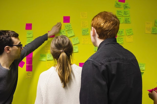 People looking at post-it notes on the wall during a GDS workshop