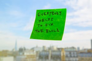 """A sticky note reads """"Everybody helps to fix the build""""."""