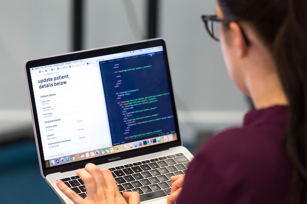 A person on a laptop with a screen showing a webpage and its code
